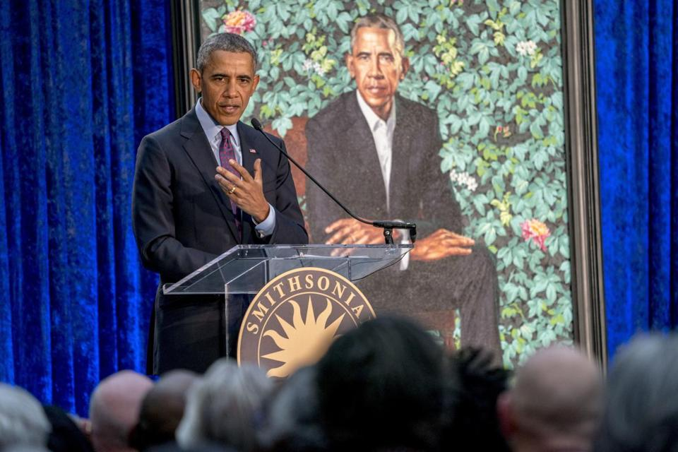 Former President Barack Obama, left, speaks at the unveiling ceremony for the Obama's official portraits at the Smithsonian's National Portrait Gallery, Monday, Feb. 12, 2018, in Washington. Obama's portrait was painted by Artist Kehinde Wiley. (AP Photo/Andrew Harnik)