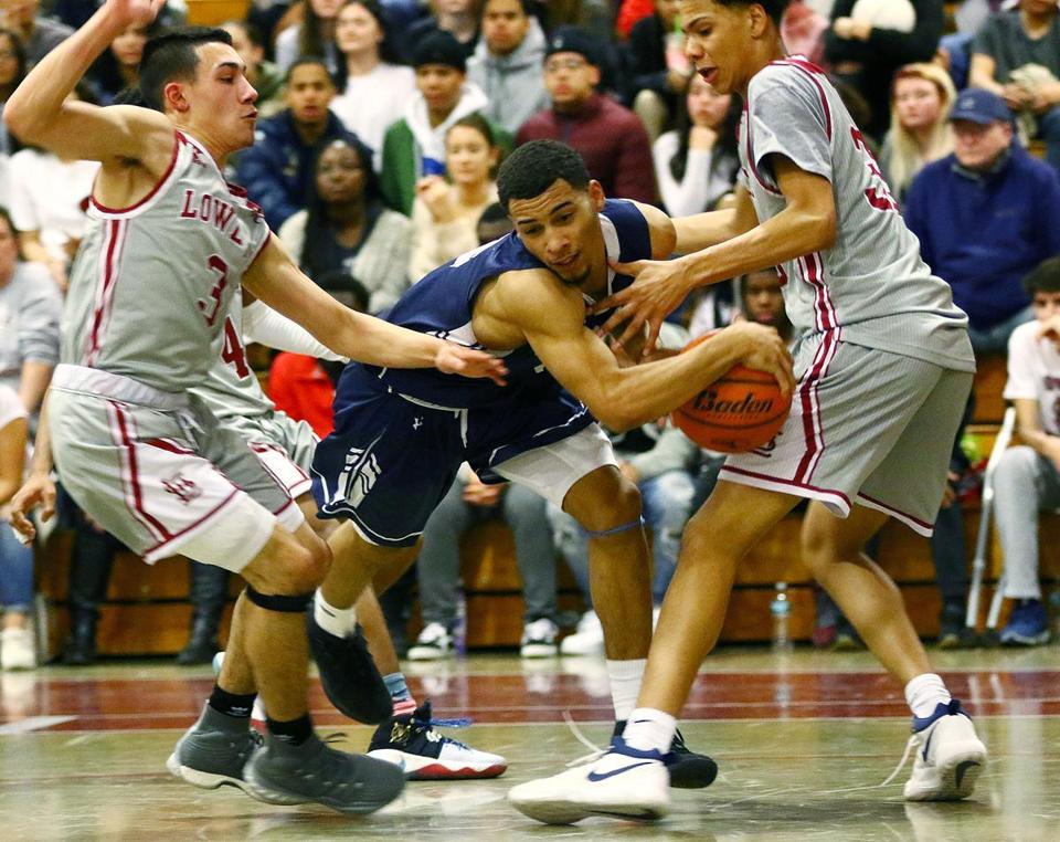 Lawrence's Juan Felix Rodriguez drives to the basket against Lowell defensive players, Carlos Nunez (#3) and Deven Okowuga, at Lowell High, Tuesday, February 13, 2018. Mark Lorenz for the Boston Globe.