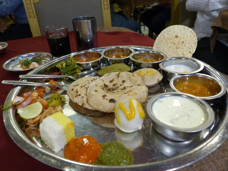 "Items at a ""thali"" restaurant in Pune, India, include a platter with curries in small bowls on the periphery, with staples in the center."