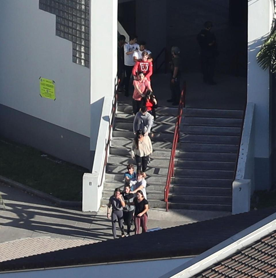 People are brought out of the Marjory Stoneman Douglas High School.
