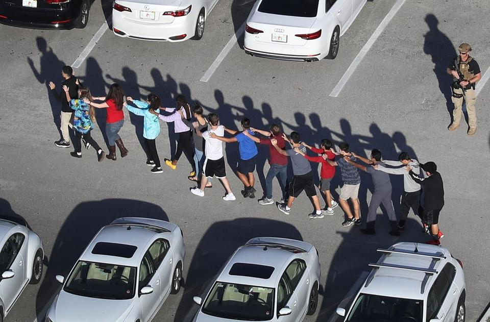 People were brought out of the Marjory Stoneman Douglas High School after the shooting.