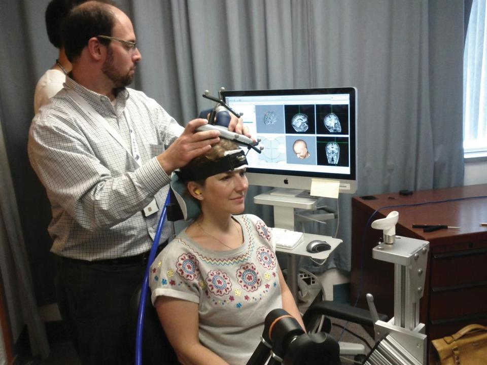 Researcher Mike Esterman applies transcranial magnetic stimulation to Caroline Williams's brain at the Boston Attention and Learning Lab at the VA Medical Center.
