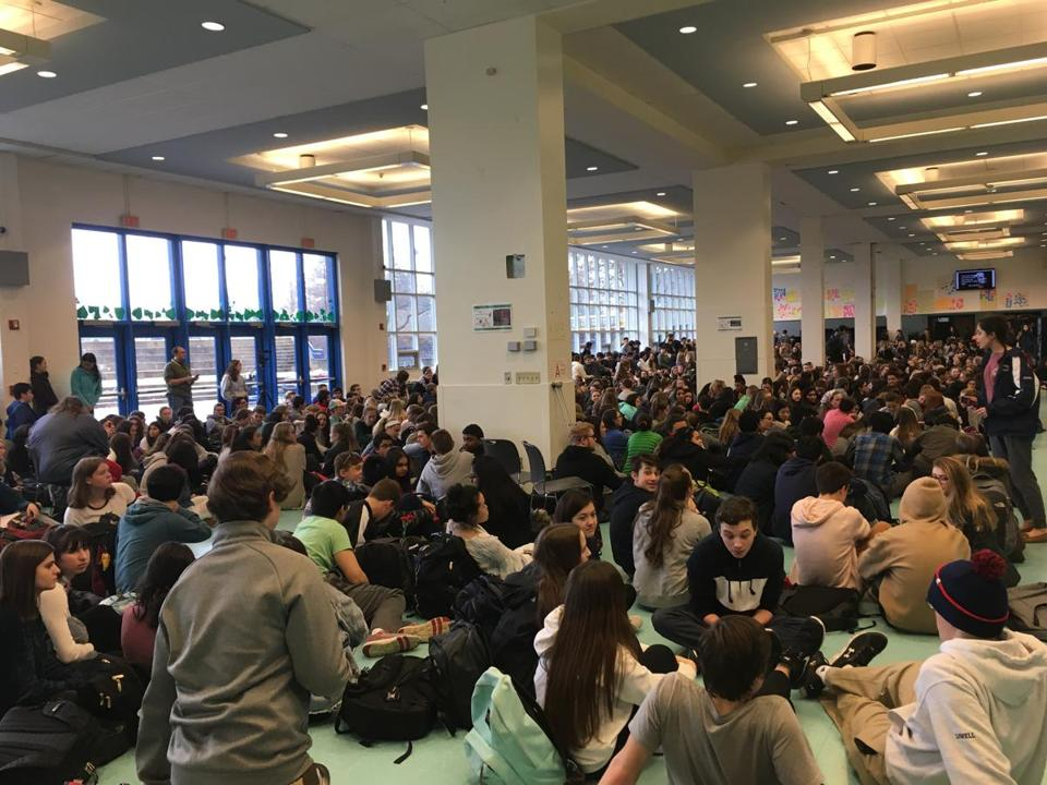 More than 100 Andover students Friday stood up, walked out of their classrooms, and gathered on the floor of the school cafeteria for a 40-minute discussion covering possible solutions to gun violence.