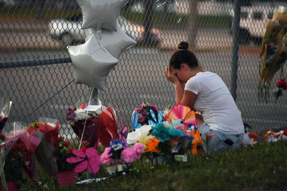 Shana Rosenthal, a student at Marjory Stoneman Douglas High School, kneeled at the fence surrounding the school on Sunday.