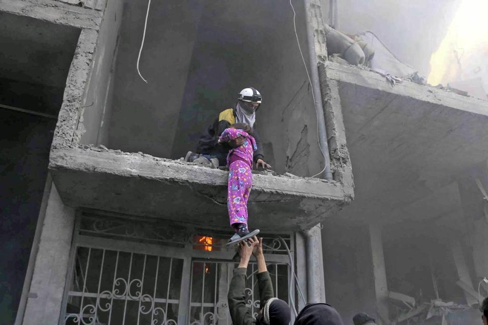 A member of the Syrian Civil Defense group rescued a young girl from a building damaged by airstrikes and shelling by Syrian government forces, in Ghouta, a suburb of Damascus.