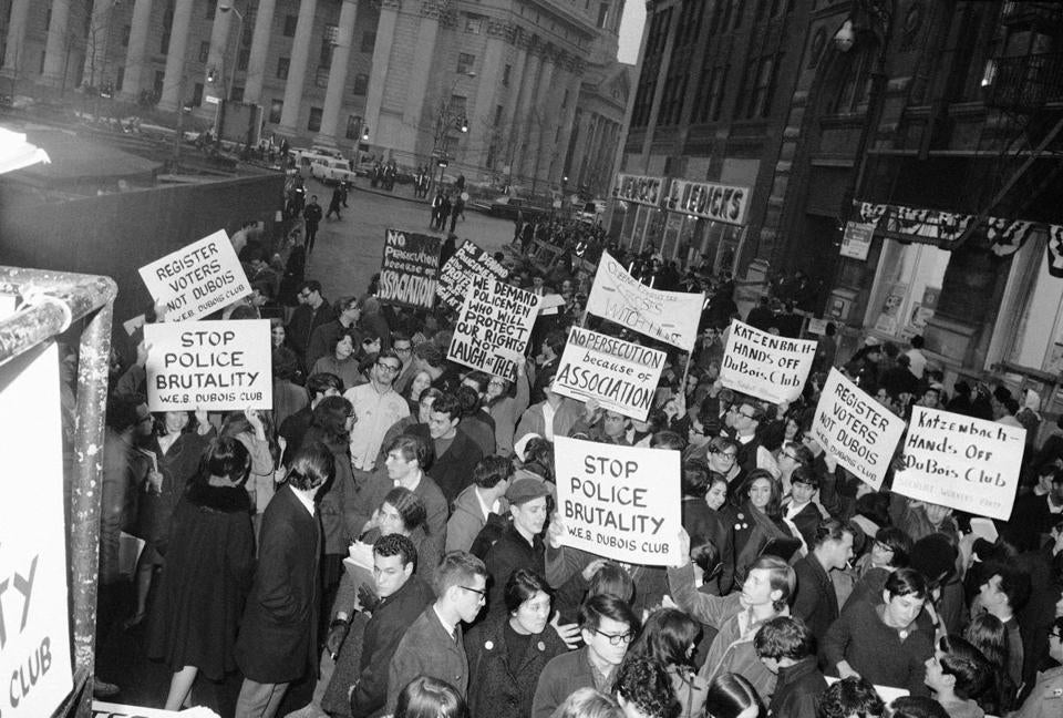 "Some 200 members of the W.E.B. Dubois Club carry banners and placards as they demonstrate in front of New York's City Hall, March 11, 1966. The youths were protesting ""police brutality"" and attorney general Katzenback's recent effort to have the organization register as a Communist front. (AP Photo/John Lindsay)"
