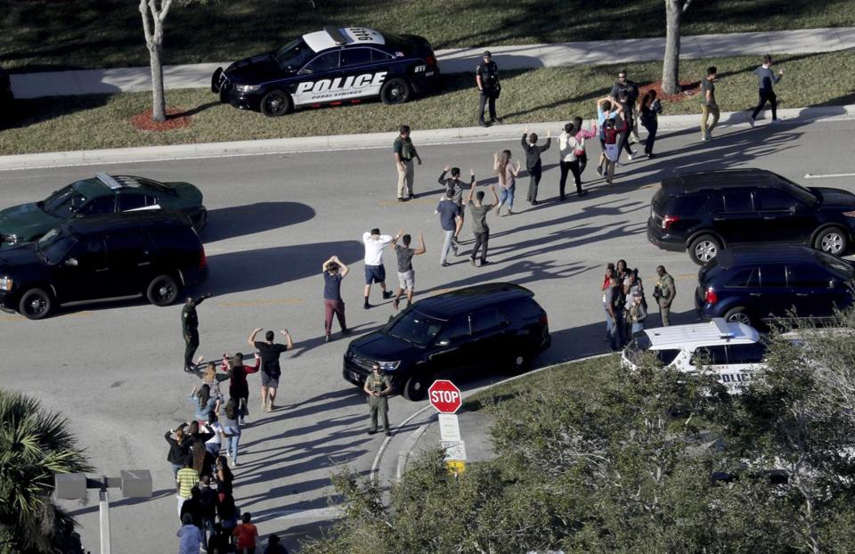 Students held their hands in the air as they were evacuated by police from Marjory Stoneman Douglas High School in Parkland, Fla.,after last week's shooting that left 17 dead.