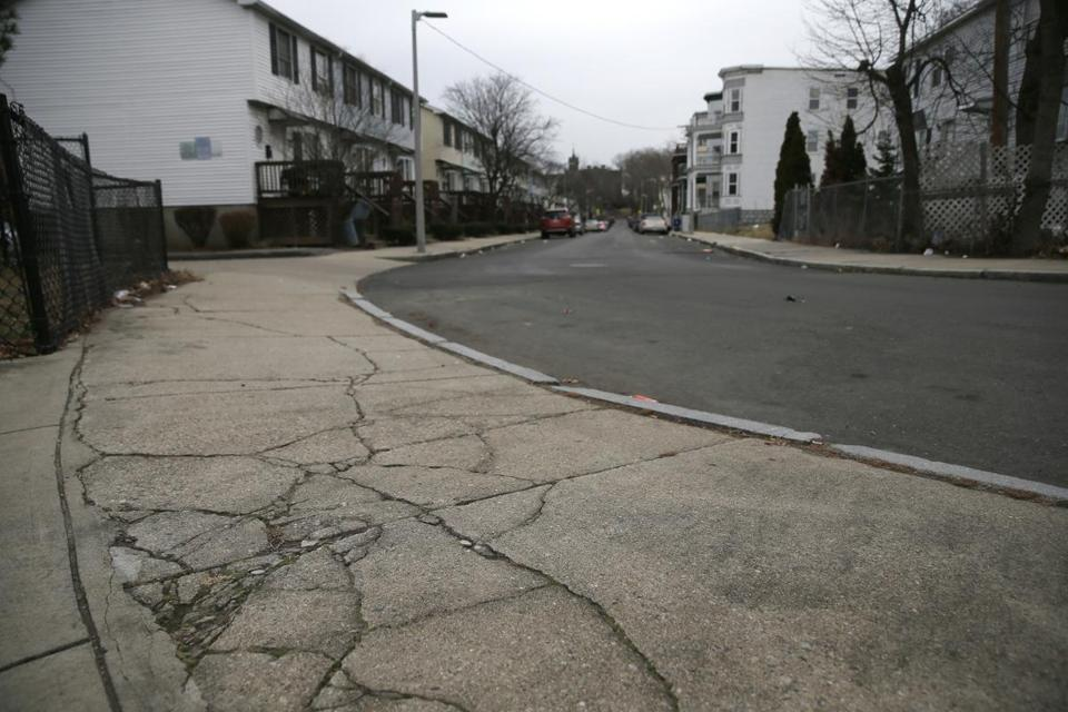 The sidewalk outside of the entrance to the playground behind the Trotter School in Dorchester is a spiderweb of cracks.