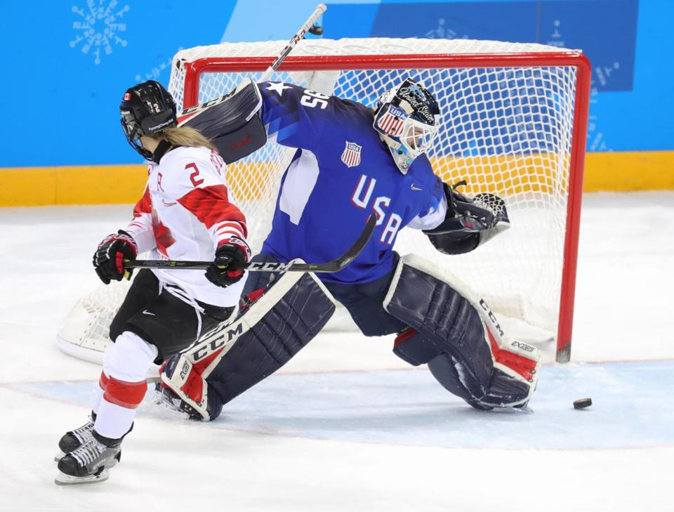 Goalkeeper Maddie Rooney makes a save on the final shootout shot by Meghan Agosta of Canada.