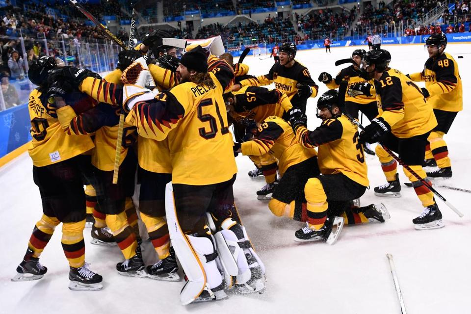 Germany's players celebrate winning the men's semi-final ice hockey match between Canada and Germany during the Pyeongchang 2018 Winter Olympic Games at the Gangneung Hockey Centre in Gangneung on February 23, 2018. / AFP PHOTO / Brendan SmialowskiBRENDAN SMIALOWSKI/AFP/Getty Images