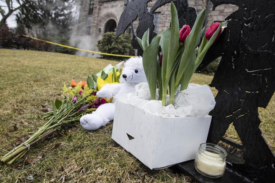 Winchester, MA - 2/25/2018 - A makeshift memorial sits on the lawn of the Winchester Public Library as a cleaning crew cleans the area where a woman is located on February 25, 2018 in Winchester, Massachusetts, fatally injured. (Keith Bedford / Globe Staff)