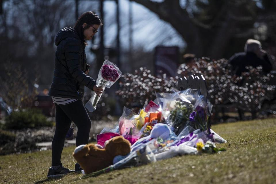 Winchester, MA - 2/27/2018 - A woman lays flowers on a makeshift memorial for Deane Kenny Stryker, a woman fatally stabbed in one of the Winchester Public Library's reading rooms, on the library's lawn in Winchester, MA, Feb. 27, 2018. The library had been closed since the stabbing over the weekend. (Keith Bedford/Globe Staff)