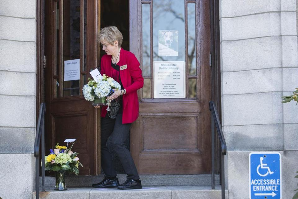 Winchester, MA - 2/27/2018 - Winchester Public Library director Ann Wirtanen picks up flowers left on the doorstep of the library to show support in Winchester, MA, Feb. 27, 2018. The library had been closed since a woman was fatally stabbed in a reading room over the weekend. (Keith Bedford/Globe Staff)