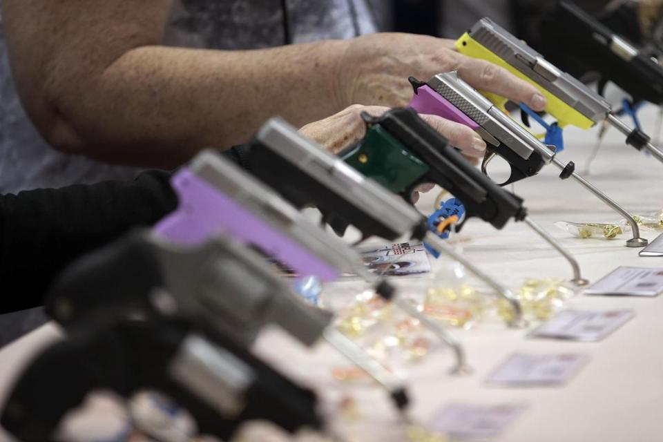 Attendees at the April 2014 NRA convention in Indianapolis checked out a pistol display.