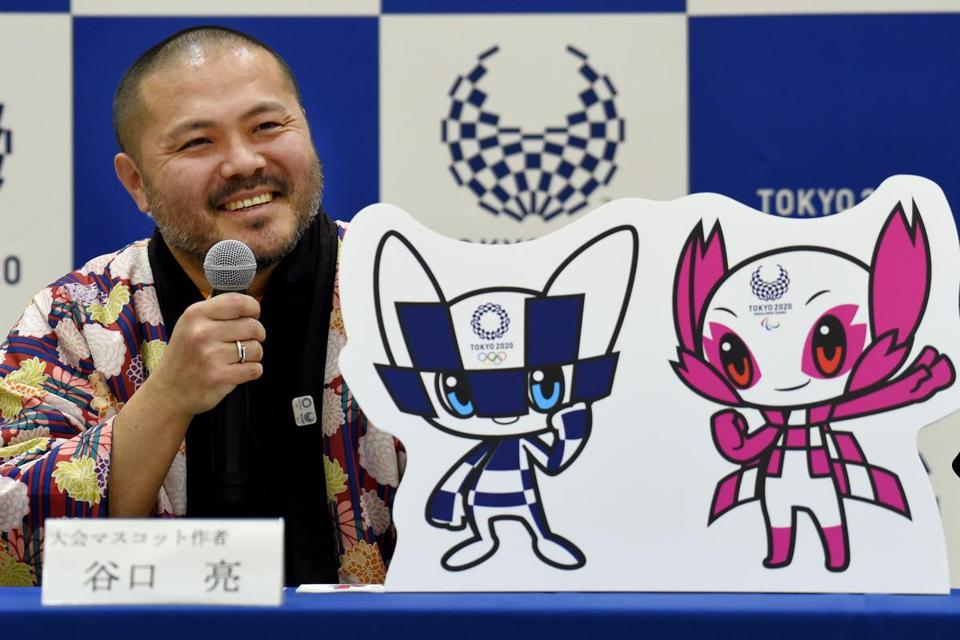 "Ryo Taniguchi, winning designer of the official mascots for the 2020 Olympics (L) and Paralympics Games, answers questions during a press conference at an elementary school in Tokyo on February 28, 2018. Tokyo on February 28 unveiled its long-awaited mascot for the 2020 Olympic Games: a futuristic blue-checked, doe-eyed character with pointy ears and ""special powers"" that was picked by schoolchildren across mascot-mad Japan. / AFP PHOTO / TORU YAMANAKATORU YAMANAKA/AFP/Getty Images"