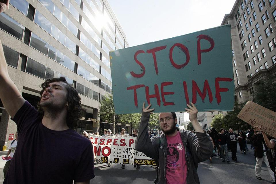 "Demonstrators march 20 October 2007 in Washington, DC, to protest the International Monetary Fund (IMF)/World Bank (WB) Fall meetings. The protesters conducted what they called a ""people's tribunal"" to condemn the effects of IMF and WB policies. AFP PHOTO/NICHOLAS KAMM (Photo credit should read NICHOLAS KAMM/AFP/Getty Images)"