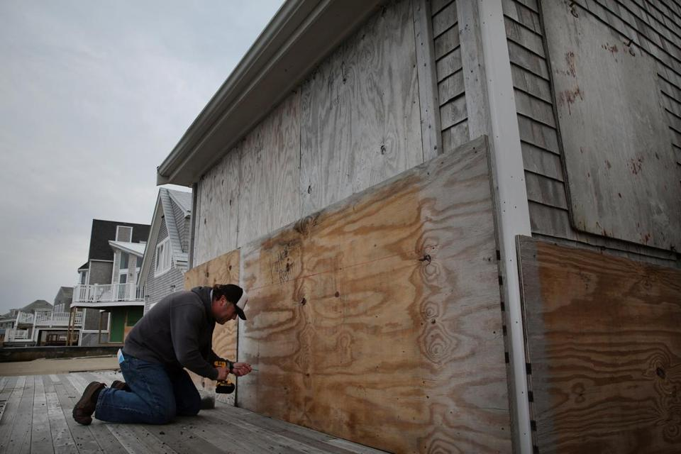 Jay Harvey worked to board up the windows of his home on Ocean Street in the Brant Rock neighborhood of Marshfield on Thursday.