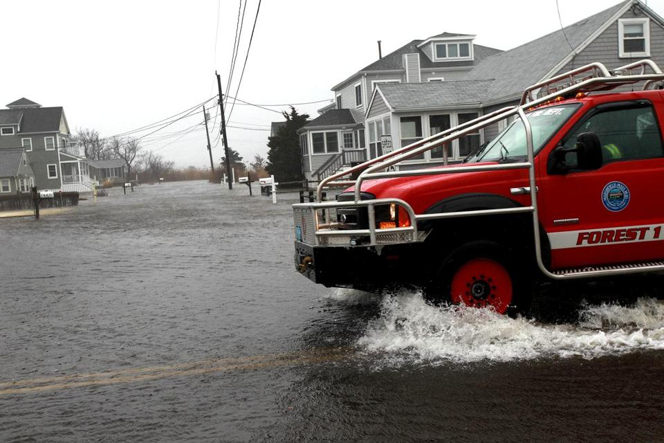 A Marshfield Fire Department vehicle patrolled a flooded neighborhood near Rexhamme Beach on Friday,