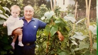 Tony D'Angelo, holding his granddaughter Julia, with his tomatoes.