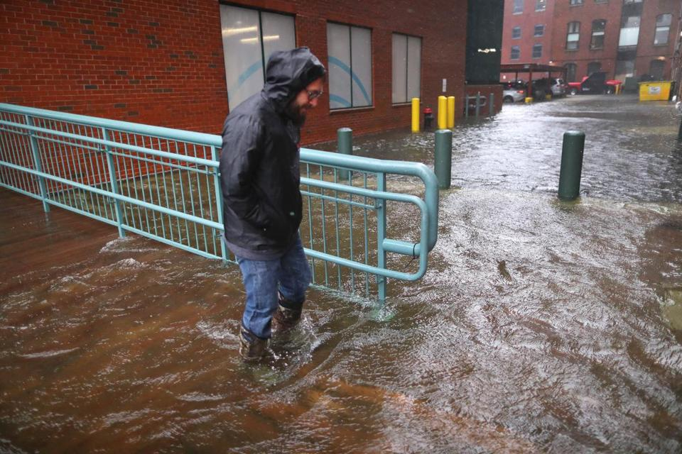 Boston-03/02/18-A man walks slowly through a flooded back street off Congress Street, where water was flowing over from Fort Point Channel in the Seaport district. John Tlumacki/Globe Staff(metro)