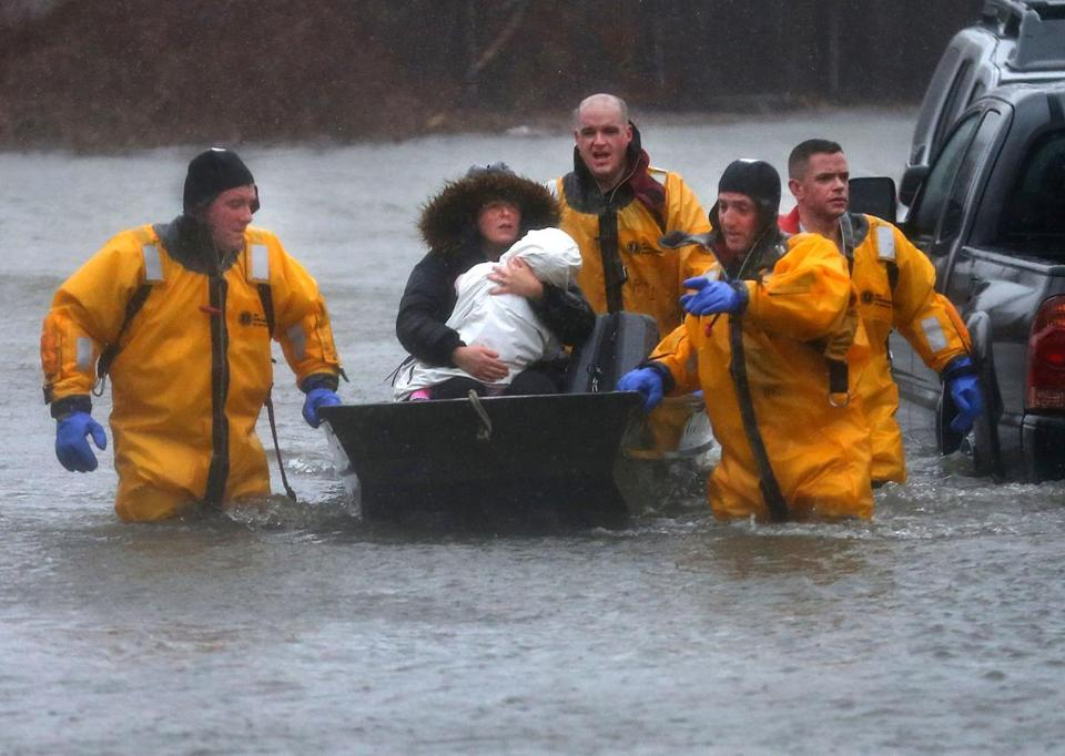 Quincy-03/02/18-A mother and child are rescued by a boat from their home. Many water rescue evacuations took place at residences flooded onPost Island Road in the Houghs Neck section of Quincy. Quincy firefighters used boats and front end loaders to rescue many residents. John Tlumacki/Globe Staff(metro)