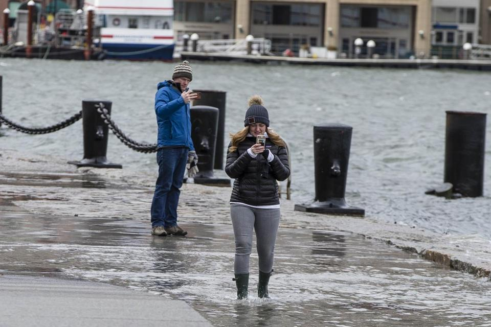 Boston, MA - 3/3/2018 - A woman walks through water as waves crash into Fan Pier along the Seaport district in Boston, MA, Mar. 3, 2018. The enormous nor'easter that brought flooding, damaging winds, and even heavy snow to parts of New England has now pushed farther out to sea. Although the storm is farther away, its influence will be felt for a couple of days. with winds and potential flooding expected. (Keith Bedford/Globe Staff)