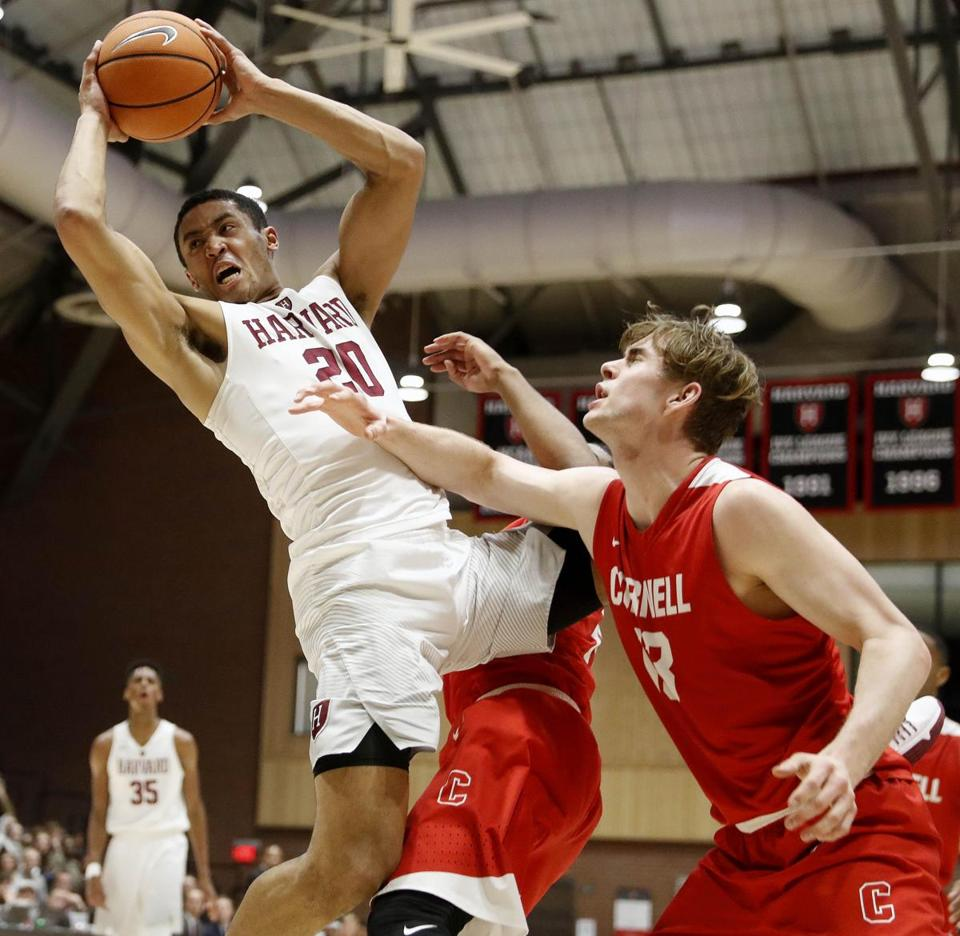 Harvard's Justin Bassey grabs a rebound over Cornell's Stone Gettings during their college basketball game in Boston Friday, March 2, 2018. (Winslow Townson for The Boston Globe)