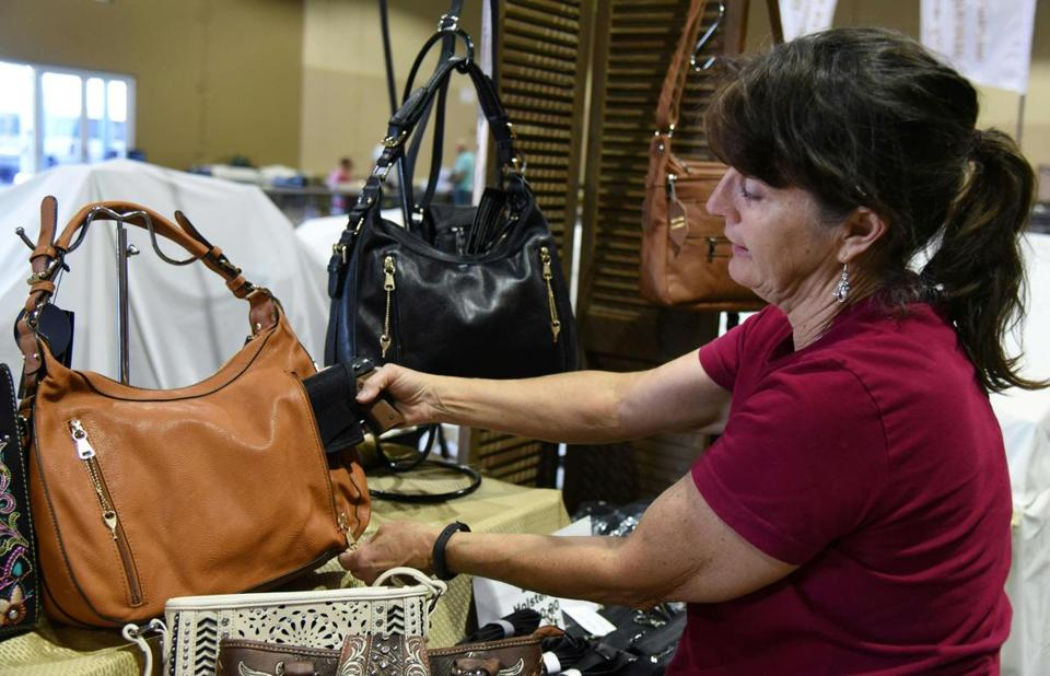 Eve Silverbach sets up her Concealed Carry Purses booth last month during preparations for South Florida Gun Show in Miami. A concealed carry fashion show will be held in Foxborough on March 9.