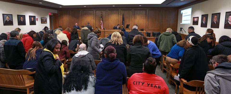 Providence, RI: 3/4/2018: The people packing the courtroom waiting to be heard by Judge Daniel McKiernan all stood as he came came onto the bench, they are pictured retaking their seats as the proceedings are set to begin. The lines were long as people waited to get into a Night Court session at the Providence Municipal Courthouse, many who were charged with speeding violations due to new traffic cameras in school zones. (Jim Davis/Globe Staff)