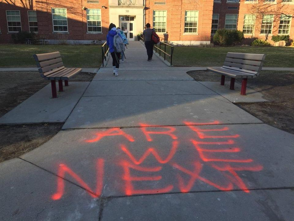 "As students trickled into the entrance to begin their day, they were greeted by the words ""ARE WE NEXT"" in bold, orange letters, painted on the sidewalk."