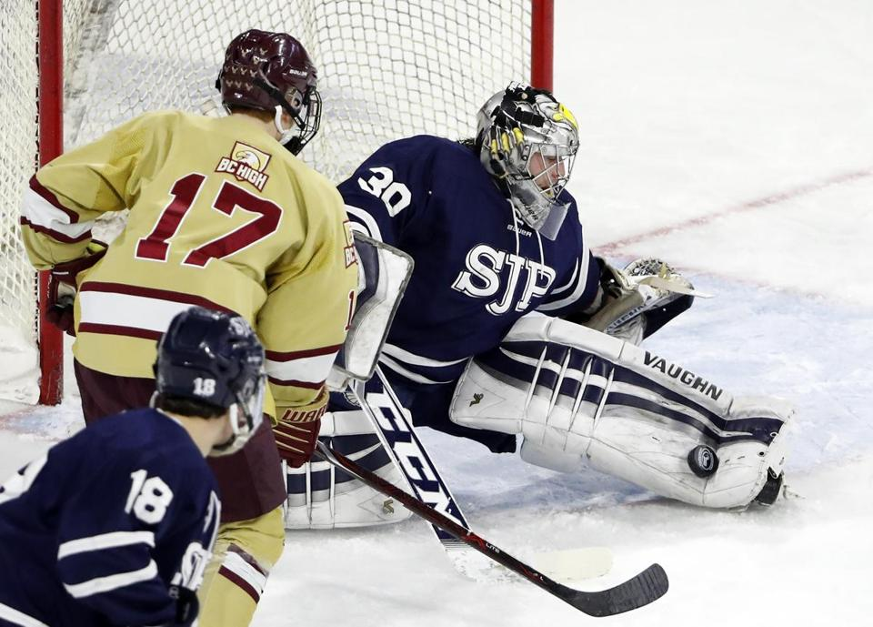 St. John's Prep goaltender Cam Ludwig made the save with BC High's C.J. Martin looking for a rebound.