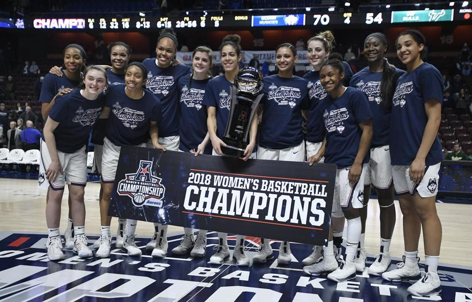 Connecticut players pose for a photograph after winning the NCAA college basketball American Athletic Conference championship against South Florida at Mohegan Sun Arena, Tuesday, March 6, 2018, in Uncasville, Conn. (AP Photo/Jessica Hill)