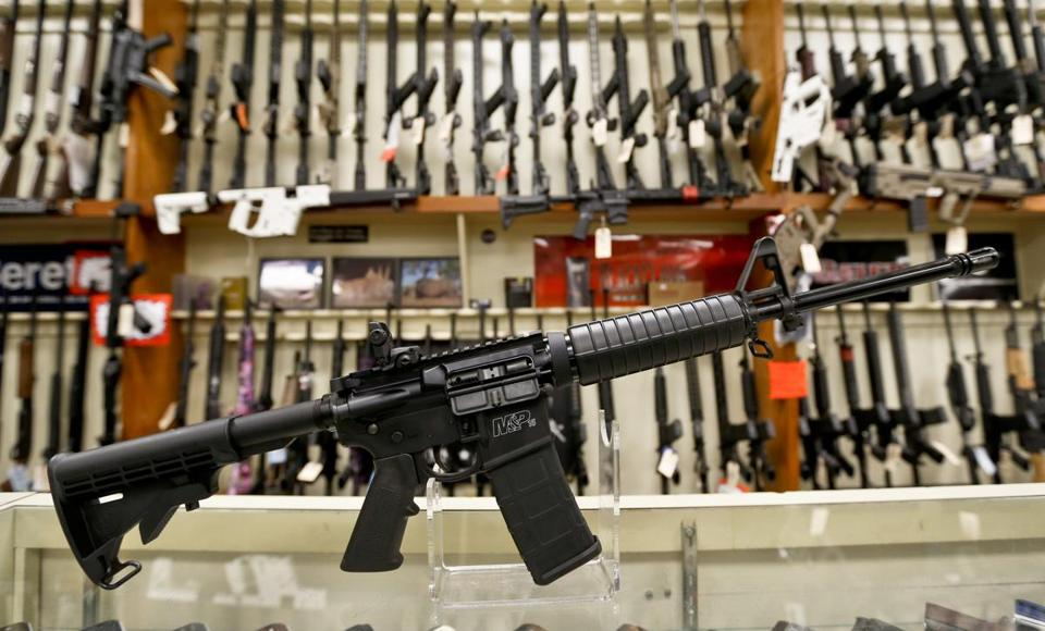 In this Thursday, March 1, 2018, photo a Smith & Wesson M&P 15 Sport rifle chambered in 5.56 mm is shown in front of a rack of other rifles at Duke's Sport Shop in New Castle, Pa. (AP Photo/Keith Srakocic)