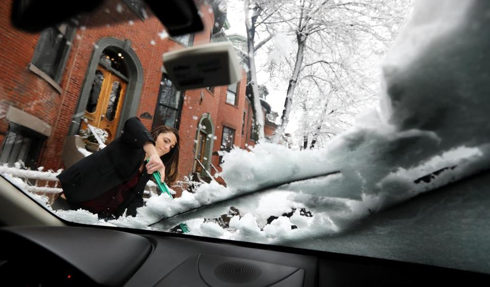 On her way to work, Alexandra Rotondo cleared snow and ice from her vehicle in the South End on Thursday.