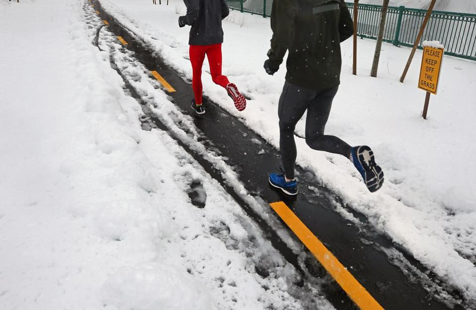 Runners kept to a small snow path on Memorial Drive in Cambridge on Thursday.