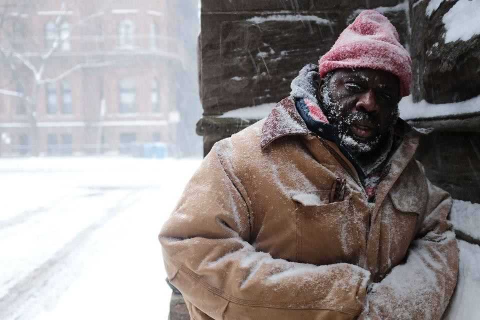 George, who is homeless, paused in a church alcove as snow fell Jan. 4.