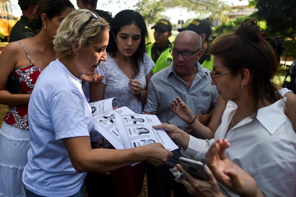 A woman handed out photocopies of ballots for one of the two main political blocs holding primary elections Colombia, after the originals ran out on Sunday in Cali.