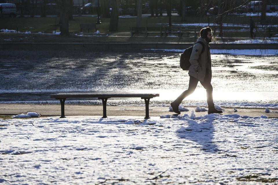 A man walked near frozen snow on the ground in the Public Garden in Boston  on