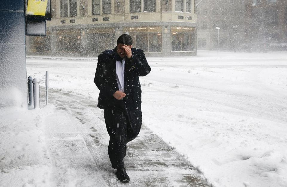 A man covered his face to protect himself from the wind as he walks down Eliot Street in Boston.