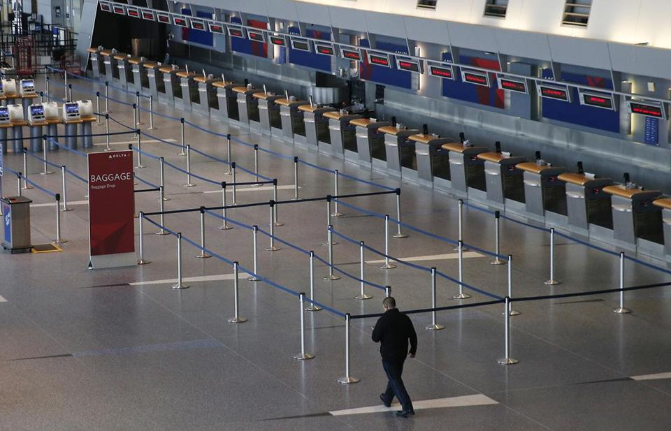SNOW SLIDER4 East Boston, MA -- 3/13/2018 - A man walked past an empty ticketing area for Delta at a deserted Logan Airport after a Nor'easter cancelled the majority of flights. (Jessica Rinaldi/Globe Staff) Topic: Reporter: snow storm nor'easter blizzard