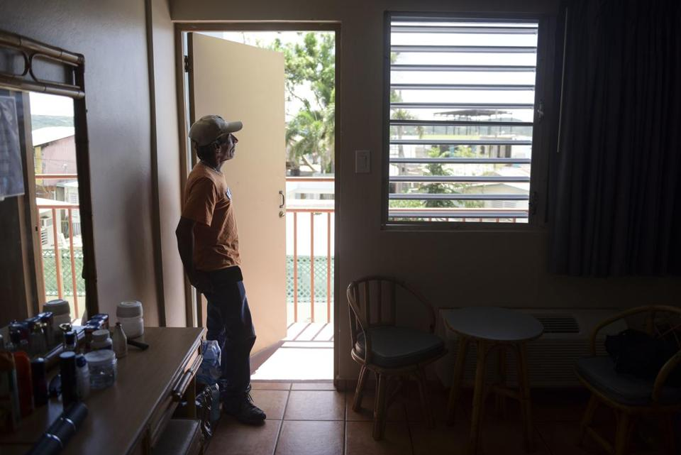 Fernando Muniz looked out from his hotel room, where he has taken refuge for months after Hurricane Maria caused damage to his San Juan residence, in Cabo Rojo.