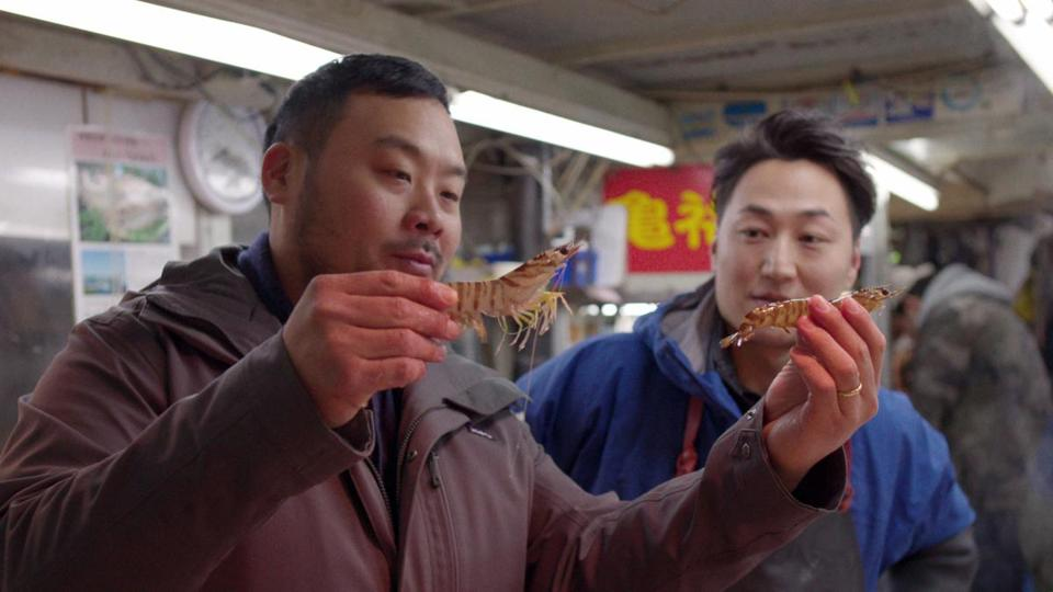 David Chang (left, with vendor Koji Namiki) compares wild and farmed shrimp in Tokyo.