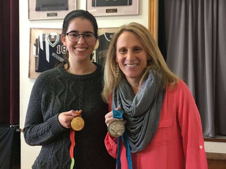 US soccer star Kristine Lilly showed one of her gold medals and her silver medal to Woodward School student and soccer player Kelly Lynch during a luncheon at the school on March 19.