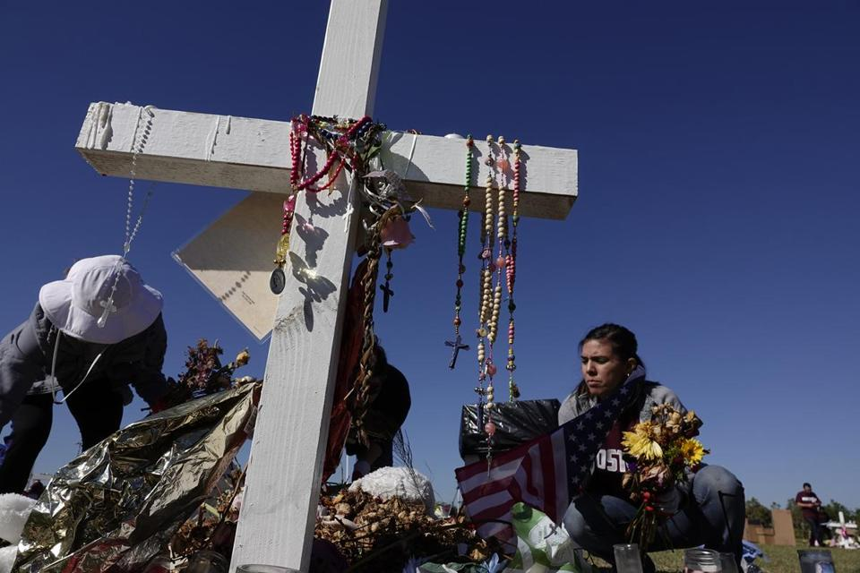 Volunteers Annabelle Andon, left, and Joanna Polk, remove items left at the memorials for the Marjory Stoneman Douglas High School shooting victims, Thursday, March 15, 2018, at Pine Trails Park in Parkland, Fla. ( via AP)