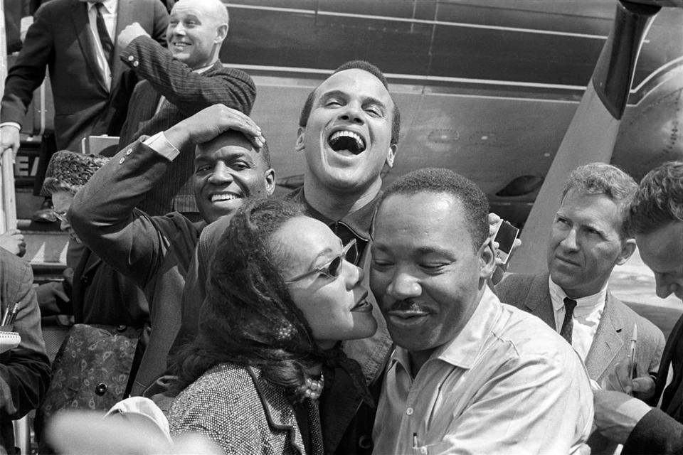 "In this 1963 image released by HBO, Dr. Martin Luther King, Jr., right, receives a kiss from his wife Coretta Scott King as they appear in Alabama with Nipsey Russell, back row left, and Harry Belafonte. The image appears in the documentary ""King in the Wilderness."" (Ivan Massar/Take Stock/The Image Works/HBO via AP)"
