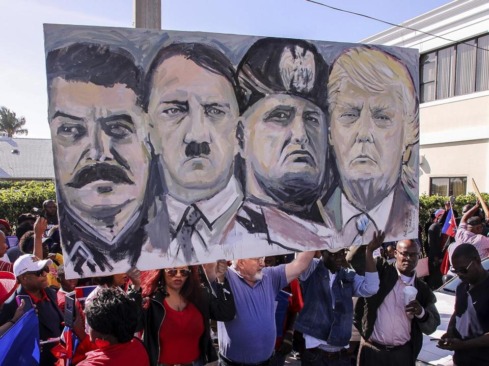 Protesters hold an image depicting (from left) Joseph Stalin, Adolf Hitler, Benito Mussolini, and President Trump during a protest near Trump's Mar-a-Lago estate.