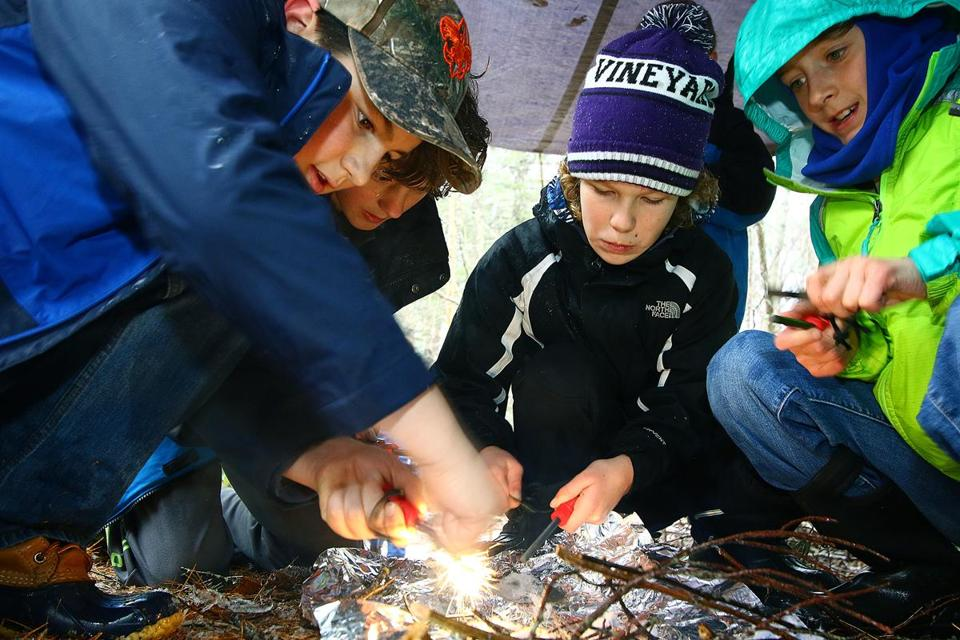 Zac Carvalho,10, Avery Cooper, 10, Lily Oliver, 9, and Cia Donohoe, 9, learn how to make a fire, as part of their survivor skills in their Boy Scouts Pack 30. The scouts are now accepting females, Pack 30, has three, Lily and Cia. Mark Lorenz for the Boston Globe.