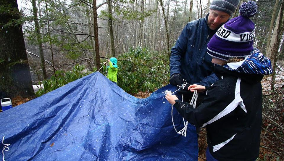 Todd Cooper, Cub Master Pack 30, teaches Lily Oliver, 9, how to make shelter, using a tarp, and a rope, by properly tiying it off. Girls are now part of the Boy Scouts, and are learning survivor skills, such as, building shelters, and starting a fire. Mark Lorenz for the Boston Globe.