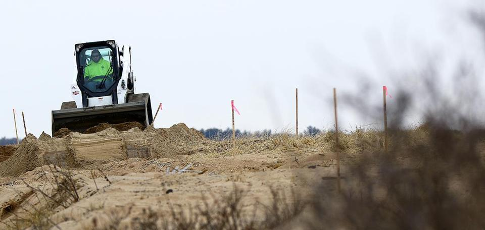 A bobcat operator works an area on the north side of Plum Island, where serious erosion is taking place, and the emergency efforts to stabilize the shore with a temporary berm. Two dunes created by the state to protect the area have washed away. Mark Lorenz for the Boston Globe.