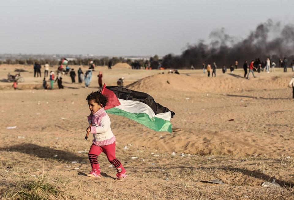 A Palestinian girls runs with the national flag, as protesters burn tires at the site of a tent protest on April 8, 2018, on the Israel-Gaza border east of Rafah in the southern Gaza Strip. Clashes erupted on the Gaza-Israel border a week after similar demonstrations led to violence in which Israeli force killed 19 Palestinians, the bloodiest day since a 2014 war. / AFP PHOTO / SAID KHATIBSAID KHATIB/AFP/Getty Images